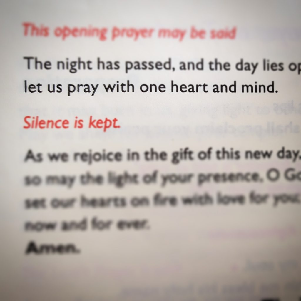 """Picture from the pages of a book with the tilt shift made to emphasise the words, """"let us pray with one heart and mind"""""""