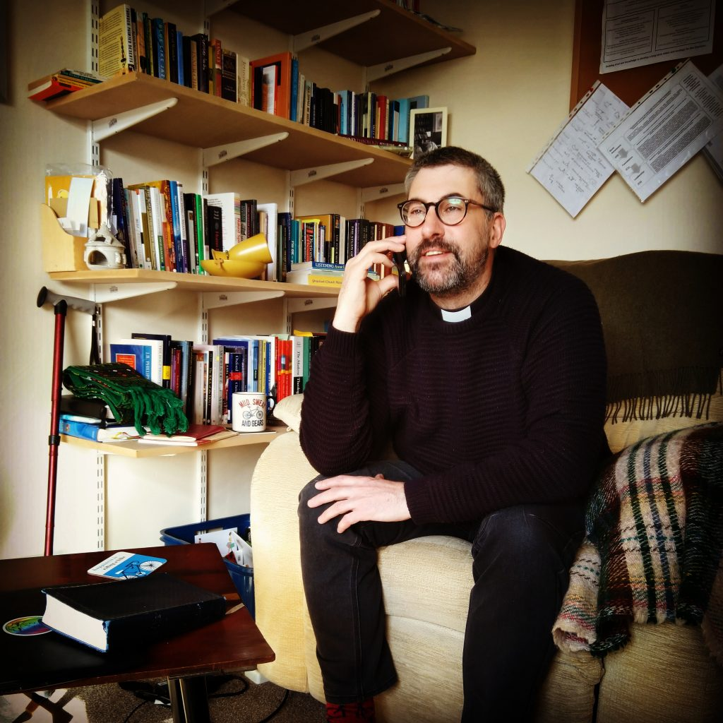 Staged photograph of a generic vicar bloke dressed in black jumper and clerical collar, holding a telephone to his ear while sitting in an armchair in front of a well-stocked bookshelf. How stereotypical.