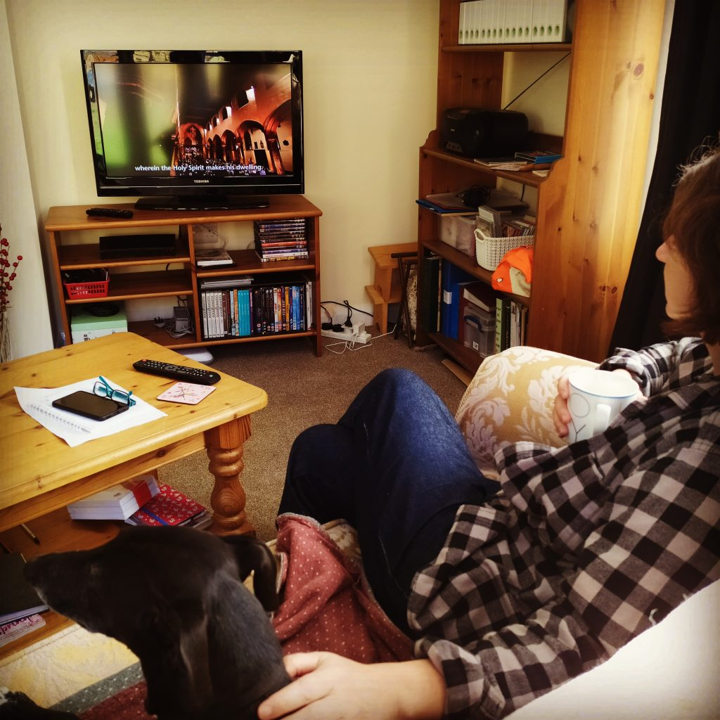 Woman on sofa with pet dog, mug of tea in hand, watching a Sunday morning worship programme on the television