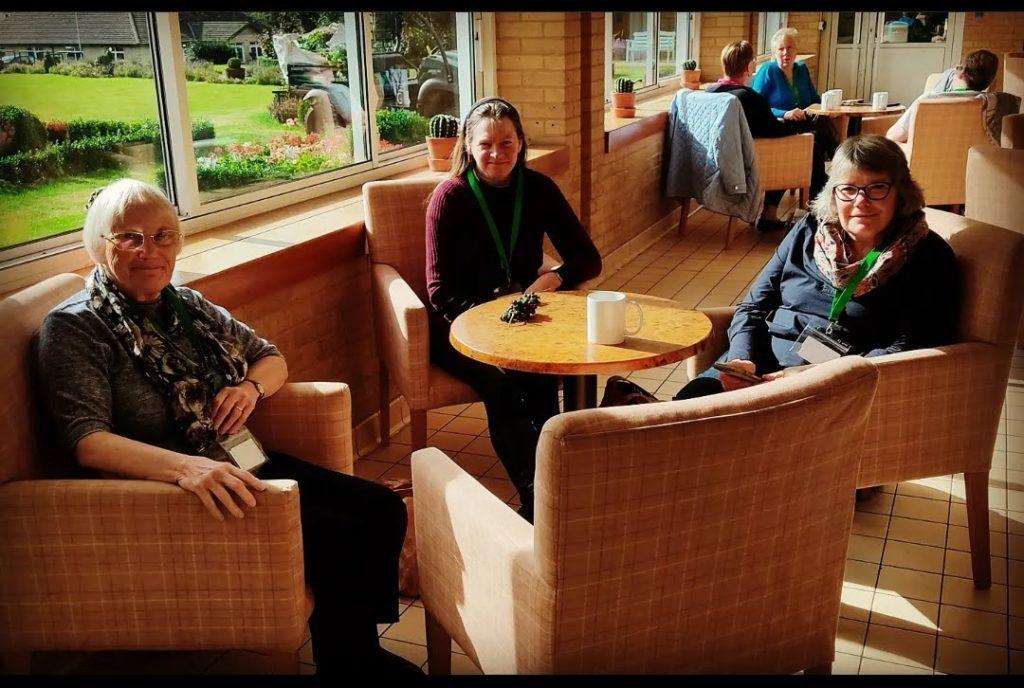 Sara, Val, Joanna sat around a coffee table in the sunshine